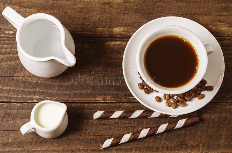 Kaffe med mjölkar och rånrullar på en träbakgrund arkivbilder