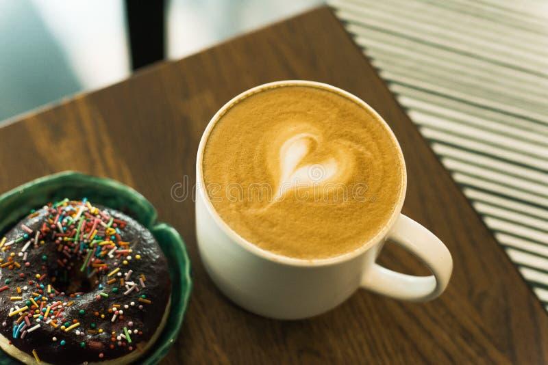 Kaffe med mj?lkar och en munk royaltyfri foto