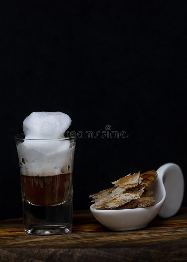Kaffe med skum i ett litet r?rexponeringsglas p? ett tr? arkivfoto