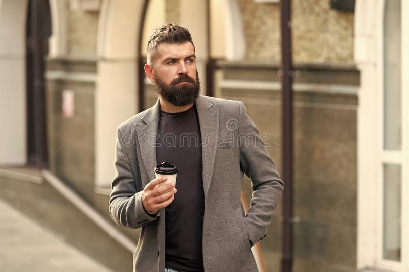 kaffe mer tid Aff?rsman i hipsterstil som rymmer takeaway kaffe Hipster med den disponibla pappers- koppen som g?r i stad arkivfoton