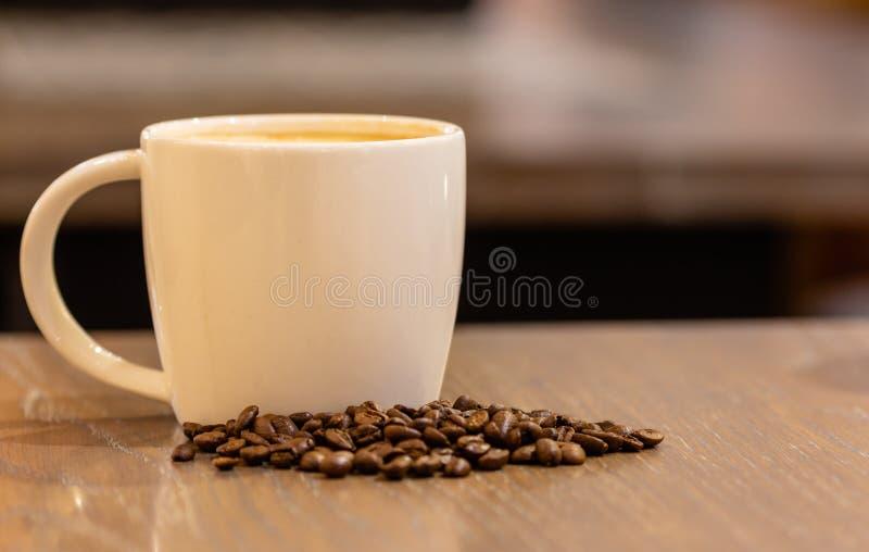 Kaffe mjölkar i en kopp med kaffebönan på trätabellen i coffee shop arkivfoton
