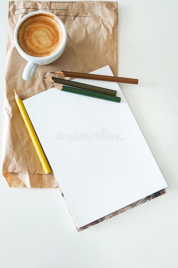 Kaffe, notepad och färgblyertspennor royaltyfri bild