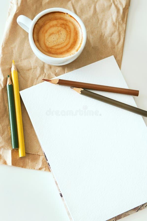 Kaffe, notepad och färgblyertspennor arkivfoton
