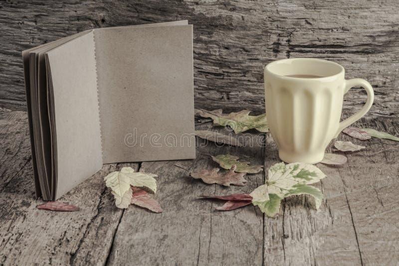 Kaffe och anteckningsboken på trätabellen dekorerade med höstsidor royaltyfria bilder