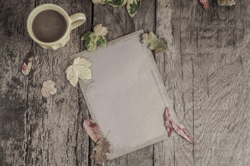 Kaffe och anteckningsboken på trätabellen dekorerade med höstsidor arkivbilder