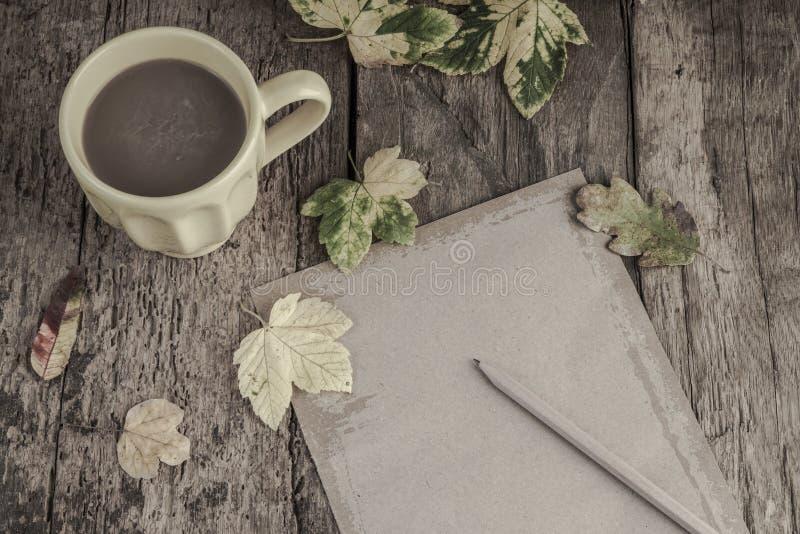 Kaffe och anteckningsboken på trätabellen dekorerade med höstsidor arkivfoto
