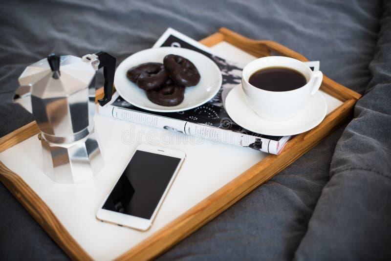 Kaffe och frukost i säng, smartphone och tidskrift arkivbild