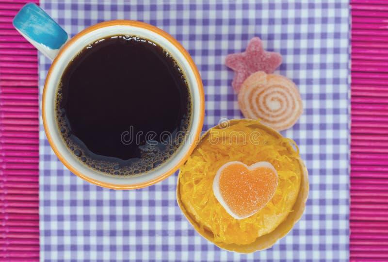 Kaffe och kaka på purpurfärgad gingham royaltyfri bild
