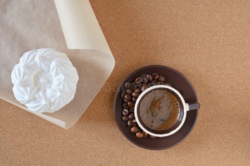 Kaffe och maräng överst av servetten royaltyfri bild