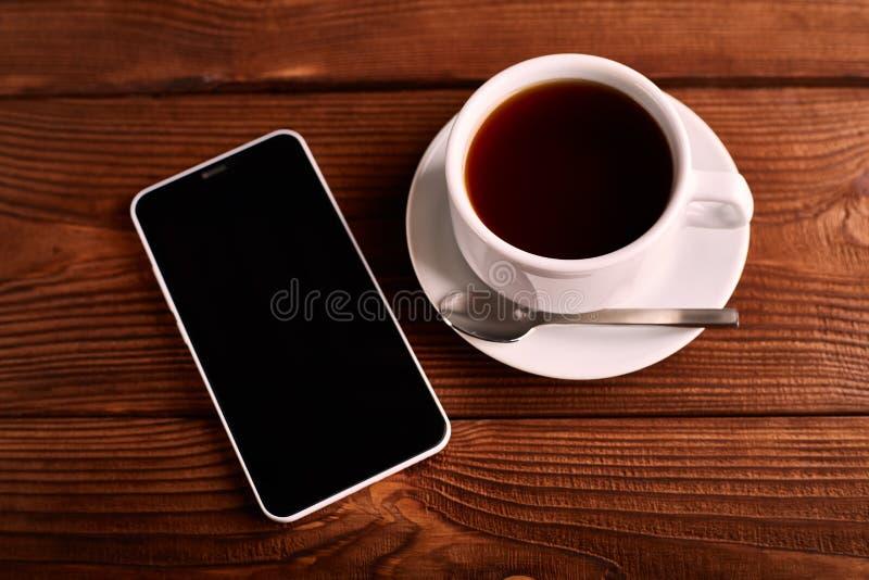 Kaffe och mobiltelefon Smartphone och en kopp av espresso på en trätabell Grejen arkivbild