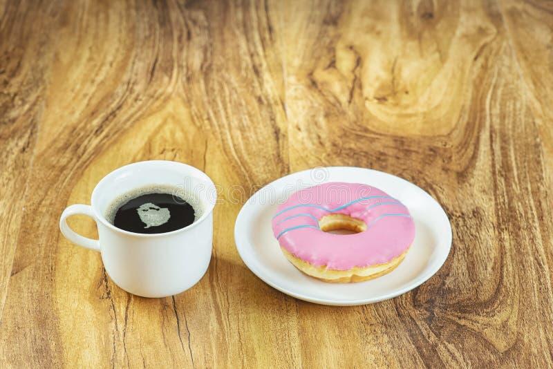 Kaffe och munk på trätabellen royaltyfri fotografi