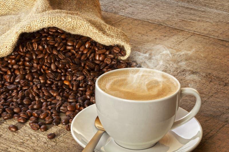 Kaffe och säck av kaffebönor arkivfoto