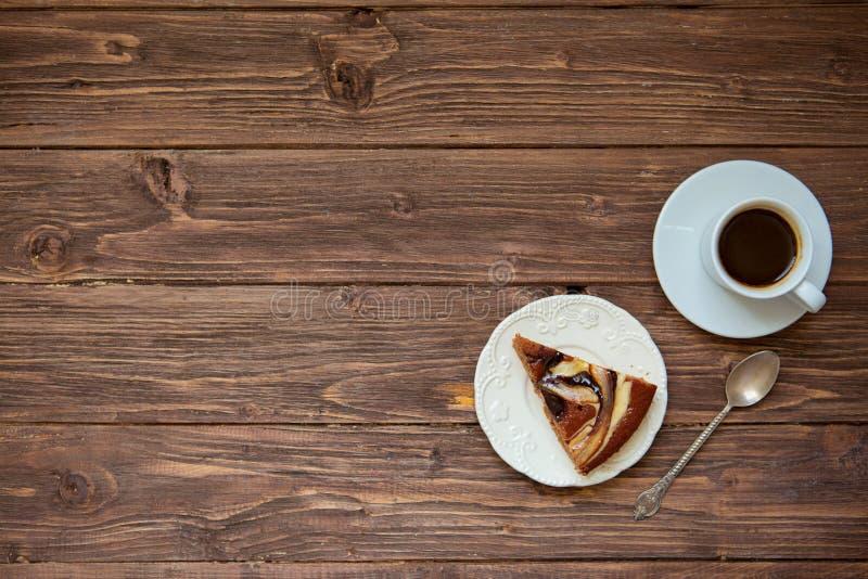 Kaffe och stycke av kakan på plattan på trätabellbakgrunden Bästa sikt med kopieringsutrymme royaltyfri fotografi