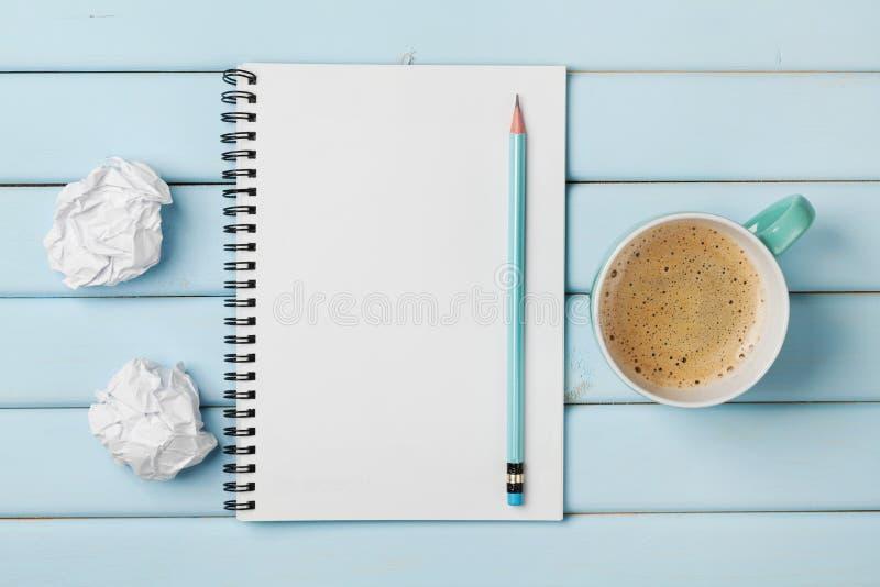 Kaffe rånar, den rena anteckningsboken, blyertspennan och skrynkligt papper på den blåa lantliga tabellen från över, idérik forsk arkivbilder