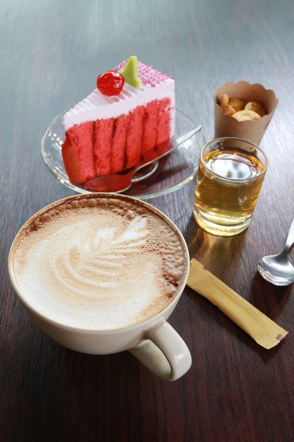 kaffe rånar och den körsbärsröda kakan på en brun trätabell arkivbild