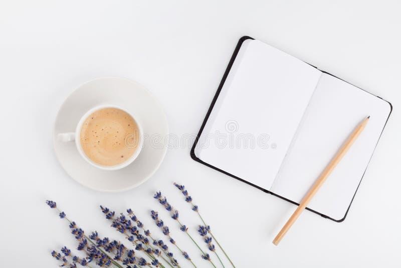 Kaffe, ren anteckningsbok och lavendelblomma på den vita tabellen från över Funktionsdugligt skrivbord för kvinna Hemtrevlig fruk royaltyfria bilder