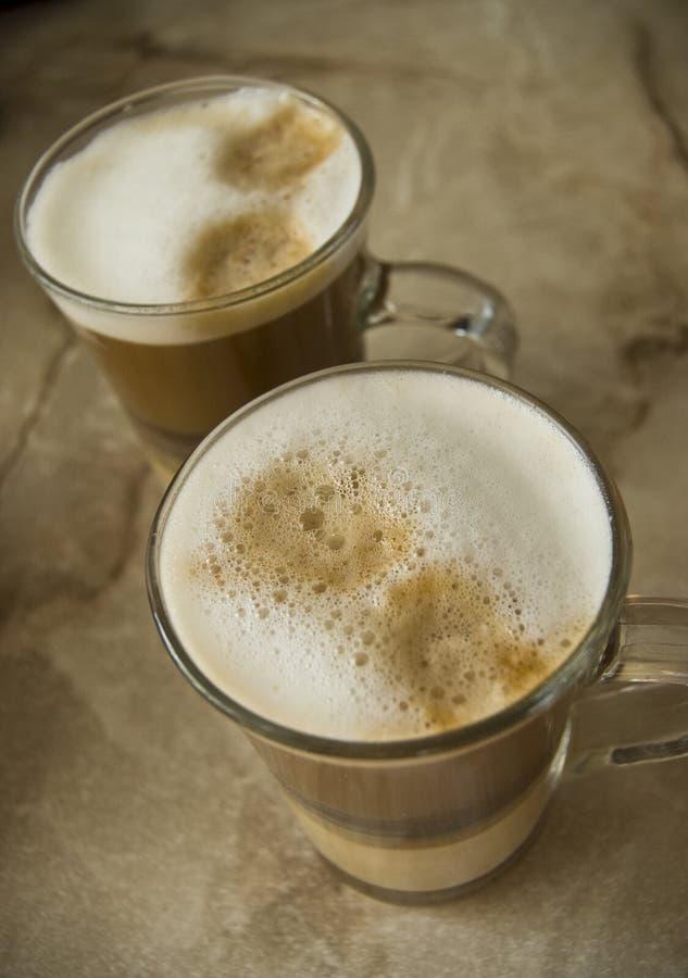 kaffe skummade exponeringsglas mjölkar royaltyfria foton