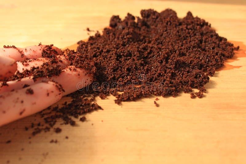 Kaffe skurar f?r framsidan och kroppen, maskeringen, sk?nhetsmedel och omsorg, v?t jordkaffetextur p? tr?bakgrund arkivfoto