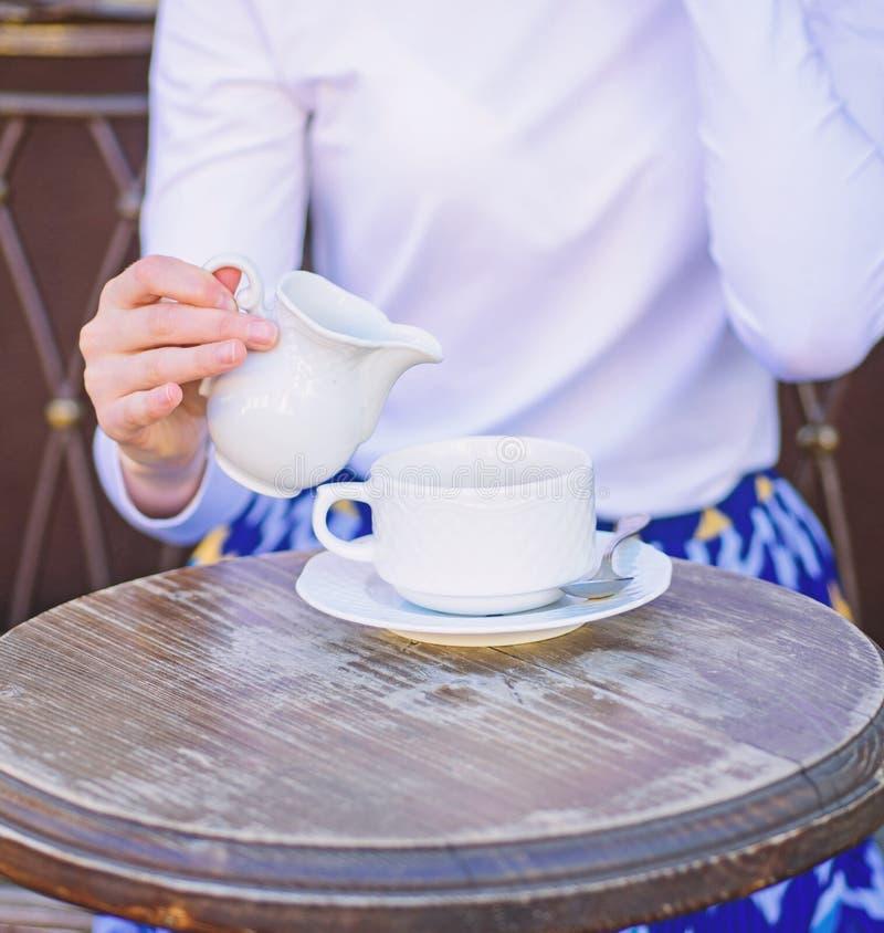 Kaffe som alltid är bättre med, mjölkar Att tillfoga för handkvinnlig mjölkar till kaféterrassen för svart kaffe utomhus, slut up royaltyfri foto