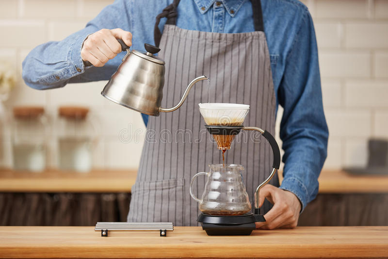 Kaffe som bryggar grejer Manlig bartender som bryggar pouroverkaffe på stången royaltyfria bilder