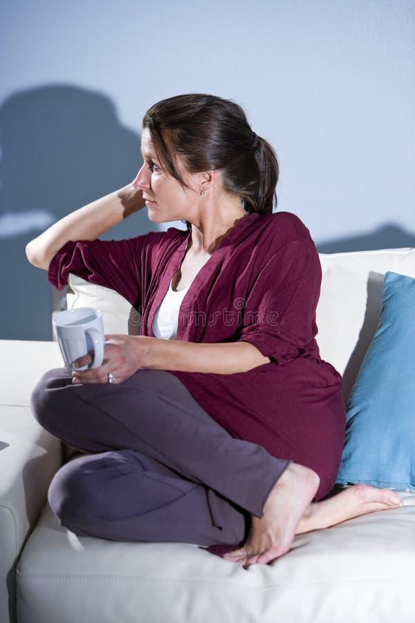 kaffe som dricker den tänkande kvinnan för eftertänksam sofa royaltyfri foto