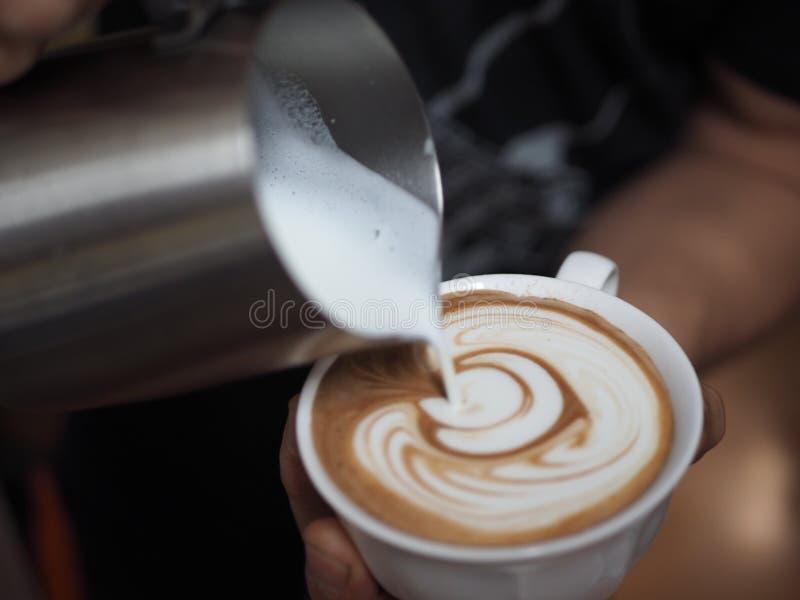 Kaffe som häller med Lattekonst arkivfoto
