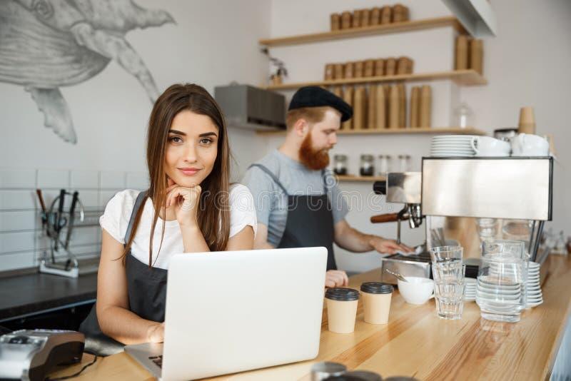 Kaffeaffärsidé - härlig caucasian bartenderbarista eller chef som arbetar och hyvlar i bärbar dator på modernt royaltyfri foto