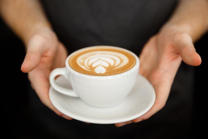 Kaffeaffärsidé - som tätt kantjusteras upp av kvinnligt portionkaffe med lattekonst, medan stå i coffee shop fokus fotografering för bildbyråer