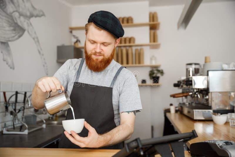 Kaffeaffärsidé - stilig skäggig man i förklädedanandekaffe, medan stå på kafét royaltyfria foton