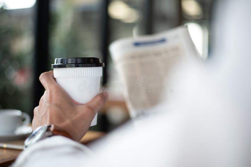 Kaffeavbrott och sökande för information om nyheterna, håll för affärsman royaltyfri foto