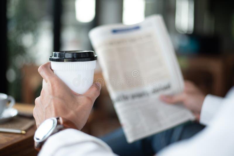 Kaffeavbrott och sökande för information om nyheterna, håll för affärsman royaltyfria foton