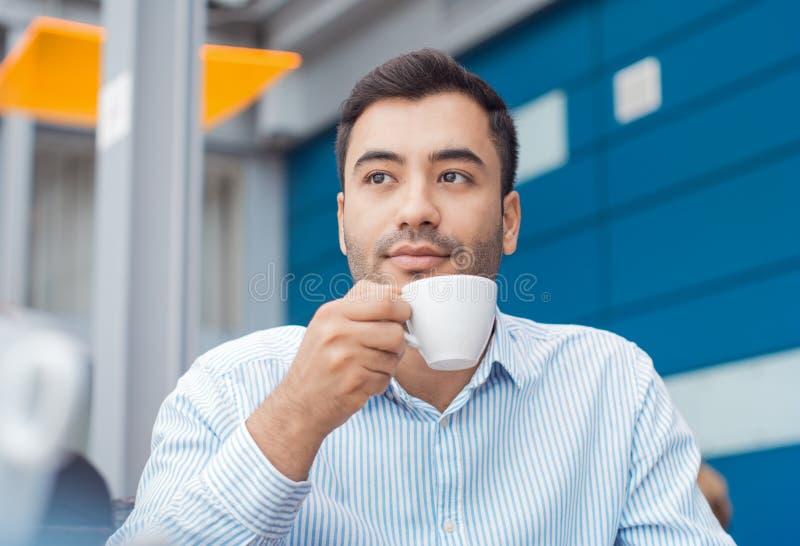 Kaffeavbrottet, mannen som vilar med varmt, dricker royaltyfri fotografi