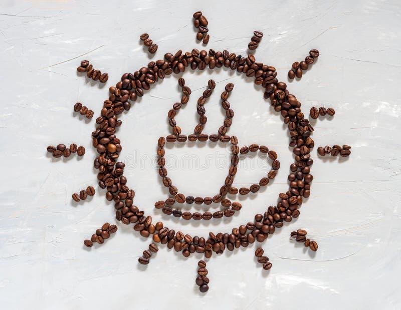 Kaffeböna i kopp- och solform på det vita golvet royaltyfri foto