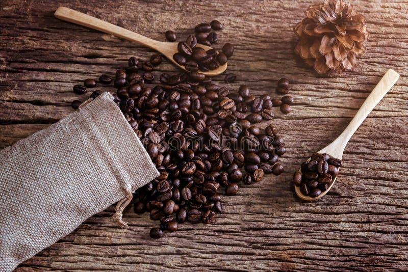 Kaffeböna i sked och påse på träbakgrund royaltyfria foton