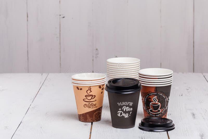 Kaffeböna med den pappers- koppen på träbakgrund royaltyfria foton