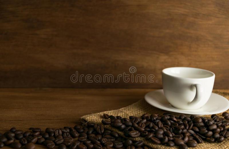 Kaffeböna och kopp kaffe på träbräde framme av brunt royaltyfri fotografi