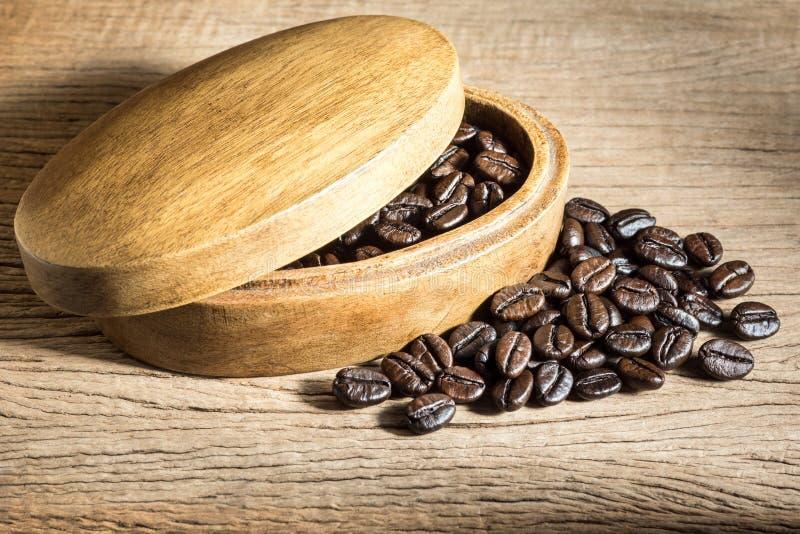 Kaffebönor i den wood asken arkivbild