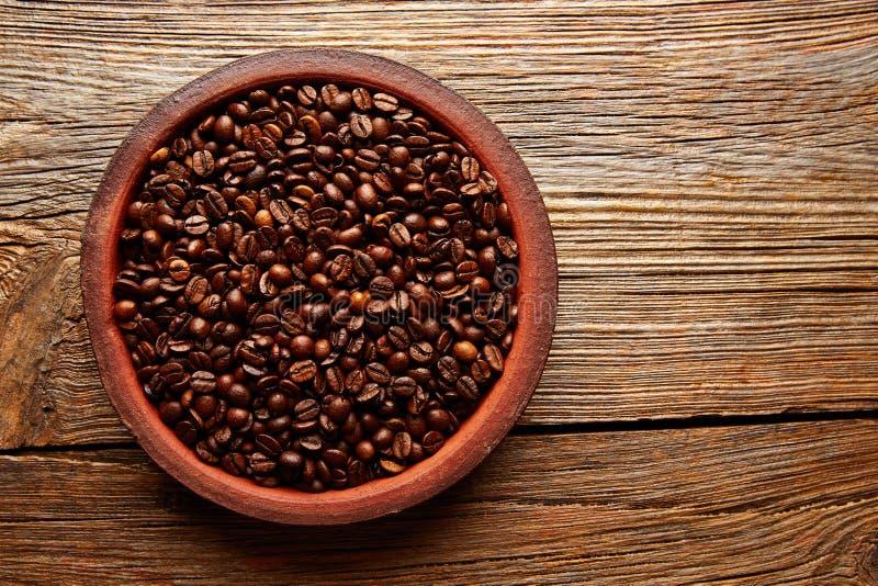Kaffebönor i en leramaträtttextur på trä arkivbild