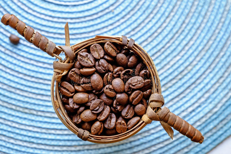Kaffebönor i en liten korglandskapöverkant royaltyfri fotografi