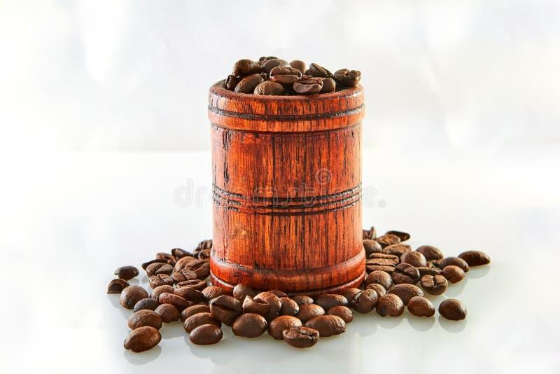 Kaffebönor i en trätrumma som isoleras på vit arkivbilder