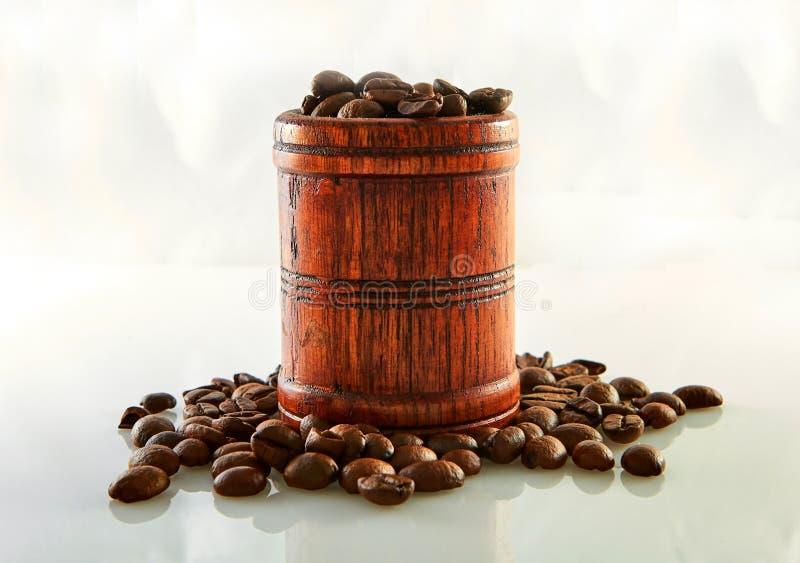 Kaffebönor i en trätrumma som isoleras på vit fotografering för bildbyråer