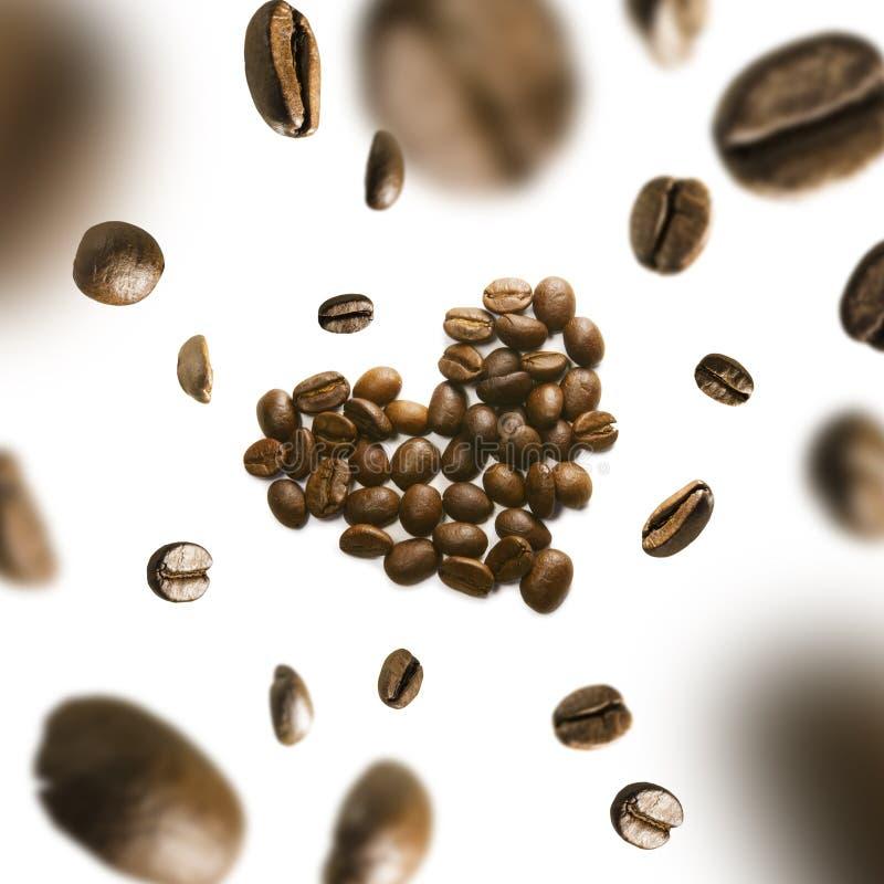 Kaffebönor i formen av en hjärta i flykten på en vit bakgrund arkivfoton