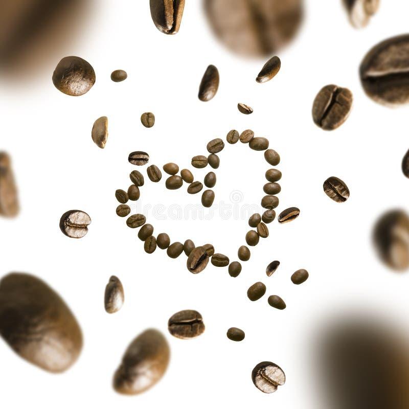 Kaffebönor i formen av en hjärta i flykten på en vit bakgrund royaltyfria foton