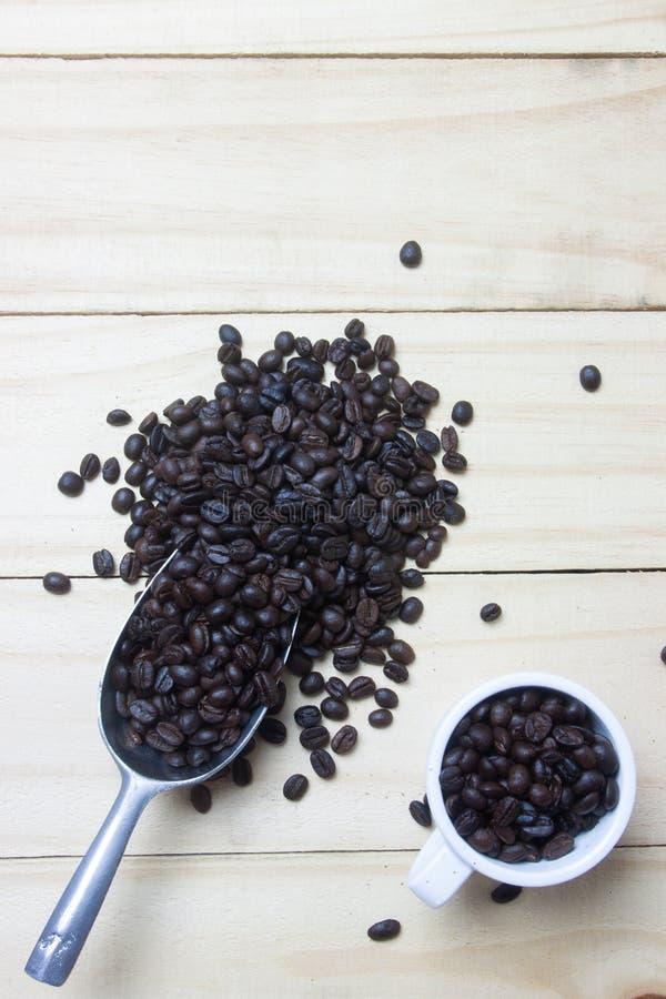 Kaffebönor i skopa på wood bakgrund arkivfoto