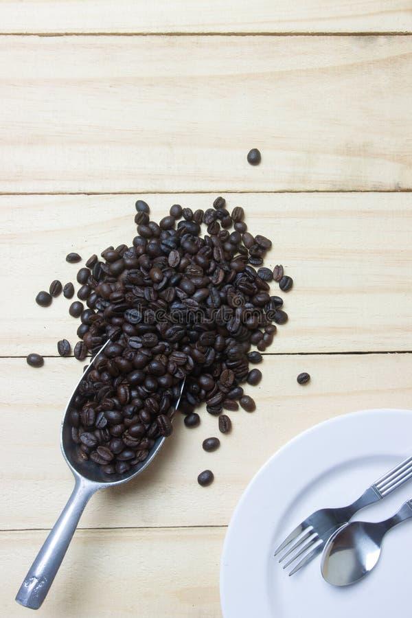 Kaffebönor i skopa på wood bakgrund royaltyfri bild