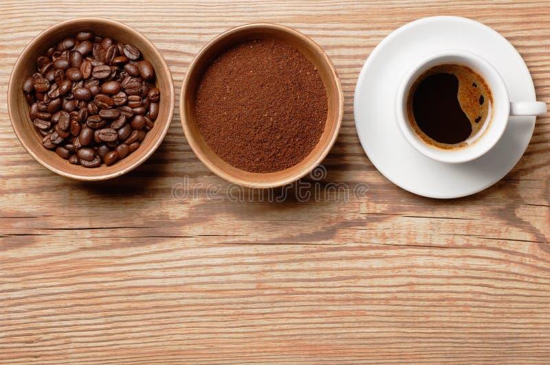 Kaffebönor, jordkaffe och kopp av brewwed kaffe på den lantliga trätabellen, bästa sikt med utrymme för text royaltyfria foton