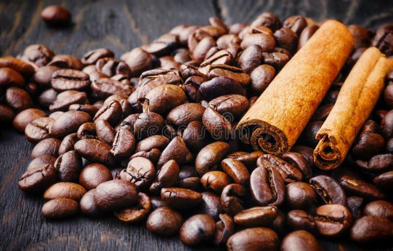 Kaffebönor, kanelbruna pinnar, arom, kaffe som är naturligt, böna, kryddor, drink, mat, brunt, på träbakgrund arkivfoto