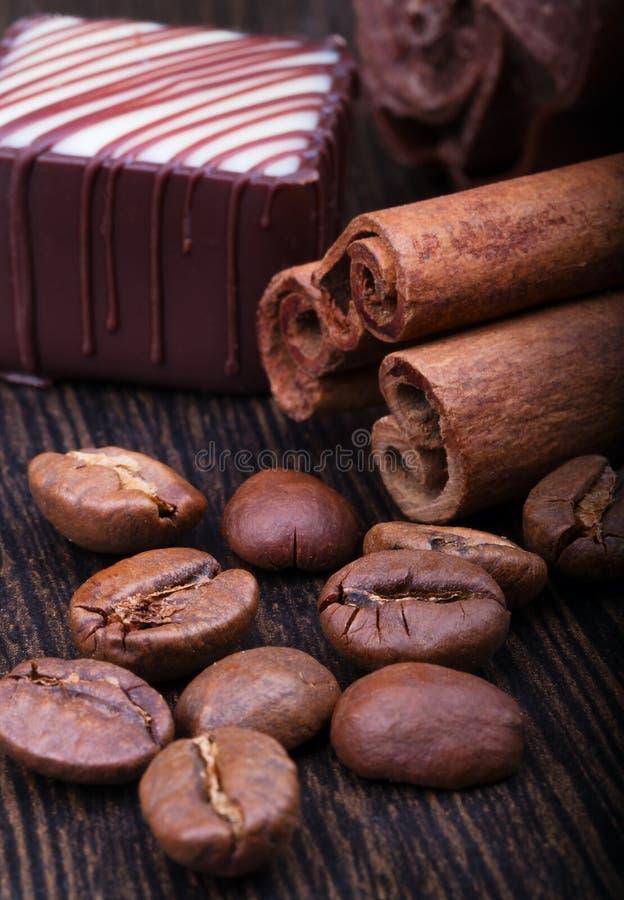 Kaffebönor, kanelbruna pinnar och choklad på träbakgrund royaltyfria foton