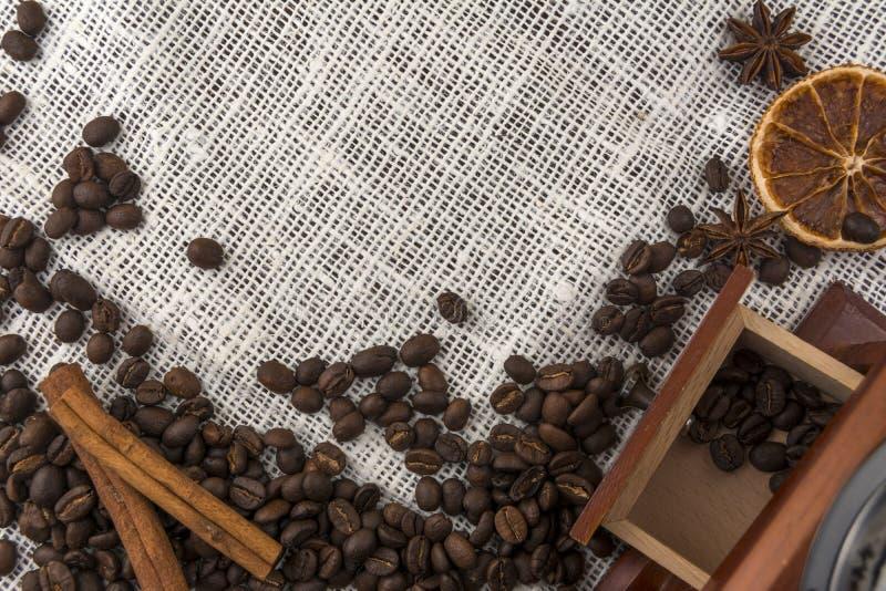 Kaffebönor, kanelbruna pinnar och en kaffekvarn på en gammal säckväv arkivbilder
