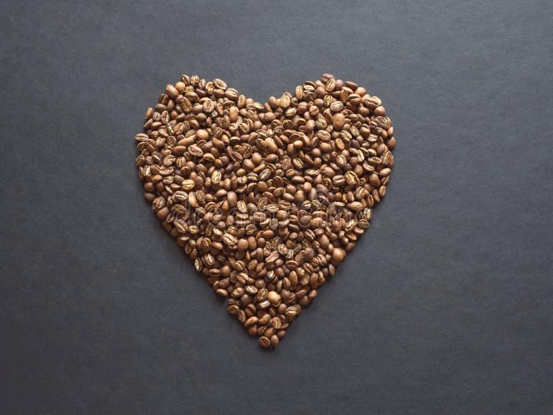 Kaffebönor läggas ut i formen av en hjärta på en svart tabell royaltyfria bilder